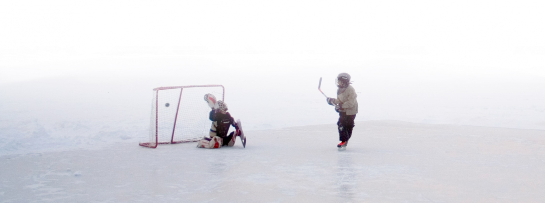 Two boys playing ice hockey on frozen lake