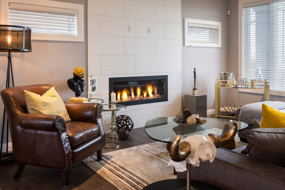 Broadview homes living room with fireplace and armchair