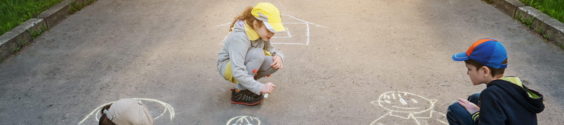 Boy and girl in hats drawing with sidewalk chalk